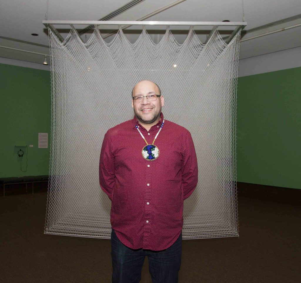 Artist Frank Shebageget in front of his work Cell