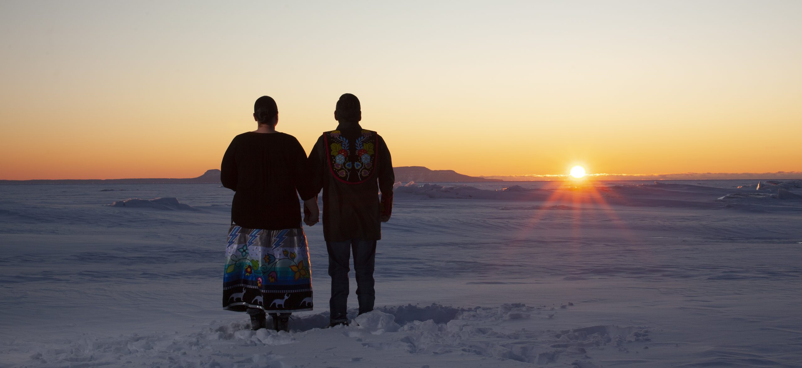Ryan and Shannon Gustafson holding hands watching the sun rise over a winter landscape photograph