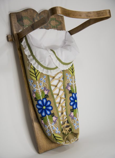 tikaangan made of wood with bead work depicting flowers and leaves